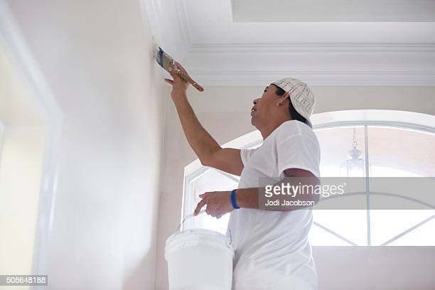 Series- Real Hispanic painter painting wall in home