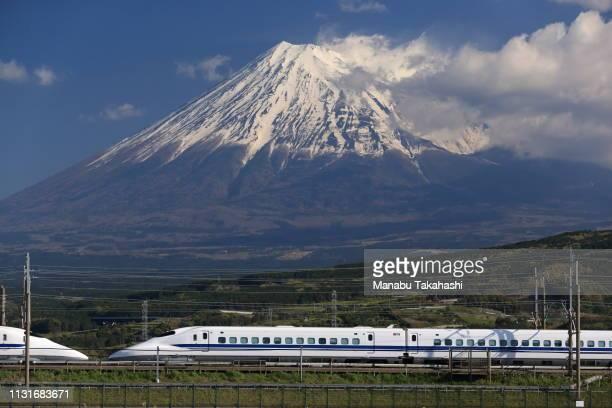 A 700 series Shinkansen bullet train runs in front of Mt Fuji between Mishima and ShinFuji stations on April 11 2013 in Fuji Shizuoka Japan