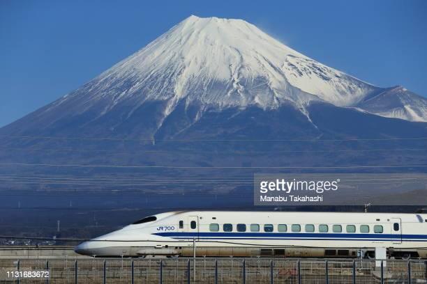A 700 series Shinkansen bullet train runs in front of Mt Fuji between Mishima and ShinFuji stations on February 17 2016 in Fuji Shizuoka Japan