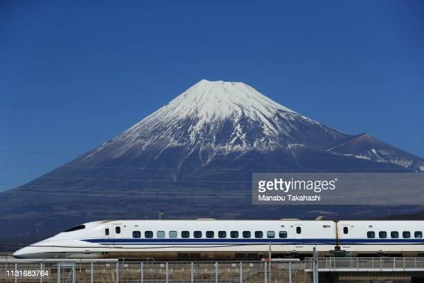 A 700 series Shinkansen bullet train runs in front of Mt Fuji between Mishima and ShinFuji stations on February 3 2017 in Fuji Shizuoka Japan