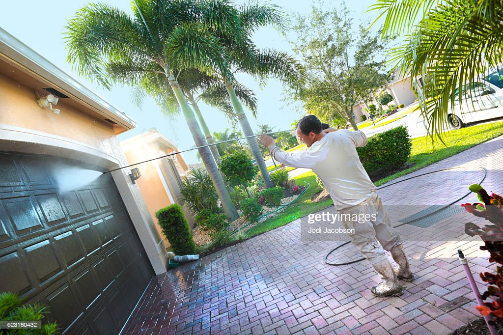 Series:Hispanic Male painter power washing an upscale home : Stock Photo