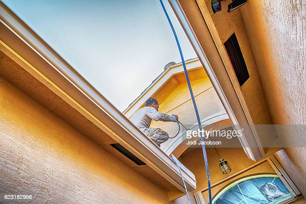 Series:House painter standing on roof spray painting entryway trim