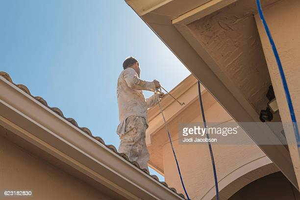 Series:House painter standing on roof spray painting trim