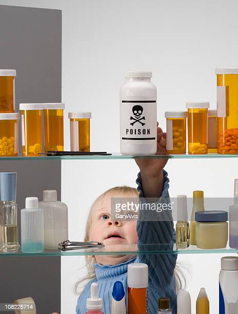 child safety series #1-little girl reaching into medicine cabinet - toxin stock pictures, royalty-free photos & images