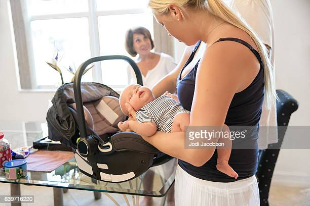 Series:Mother putting sleeping infant son into car seat carrier