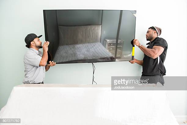 Series-Real televison installers hanging large flat screen TV on wall