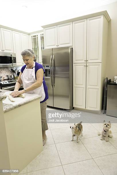 Series:Senior caucasian woman rolling bread dough with two dogs watching