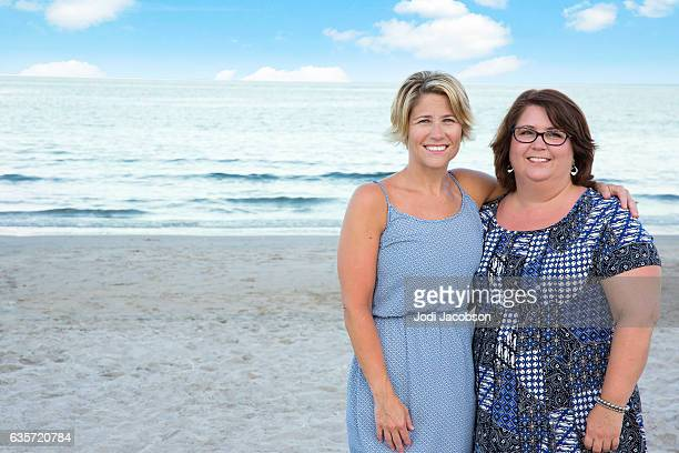 series:two adult sisters at beach contrast in coloring and build - fat woman at beach stock photos and pictures
