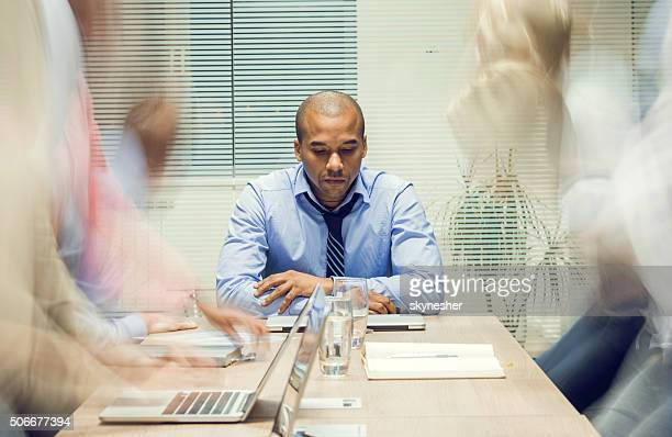 Serious African American businessman in board room.