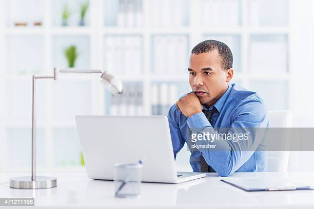 Serious African American businessman working on laptop in office.