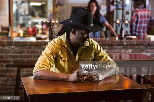 Serious African American Man Drinking Beer Alone In Bar
