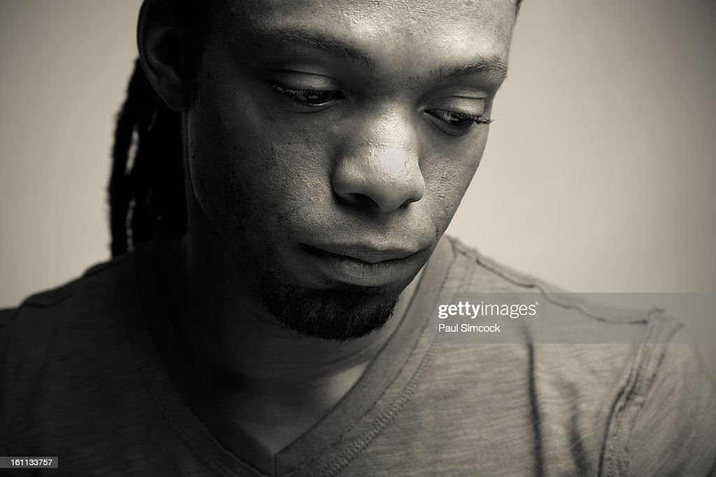 Serious African American man looking down : Stock Photo