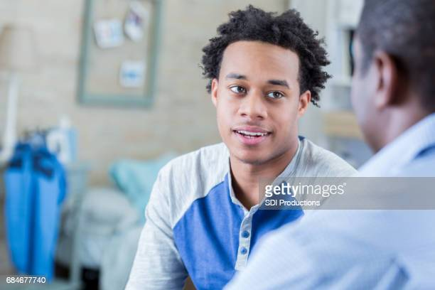 Serious African American teenager has conversation with his dad