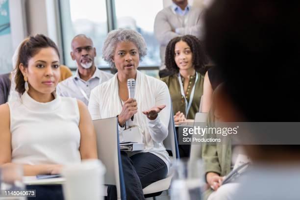 深刻なアフリカ系アメリカ人の女性が会議中に質問をする - パネル討論 ストックフォトと画像
