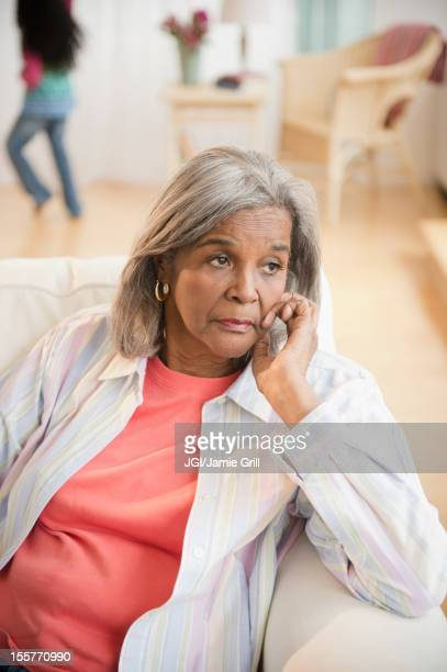 Serious African American woman sitting on sofa