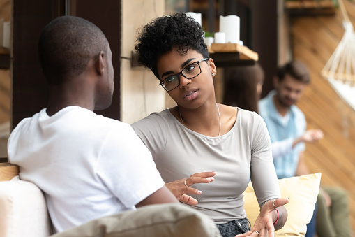 Serious African American woman talking with man in cafe 1083813356