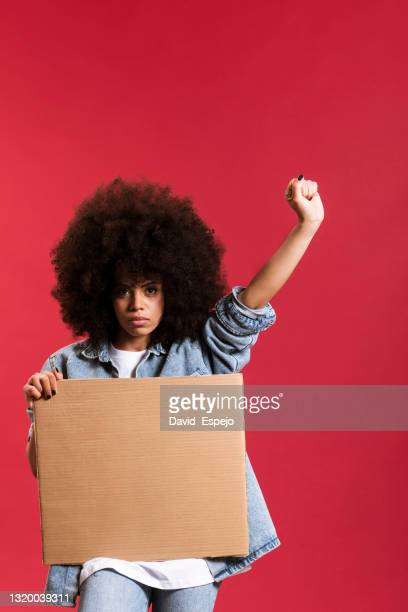 serious afro woman holding a placard against a red background. - anti racism stock pictures, royalty-free photos & images