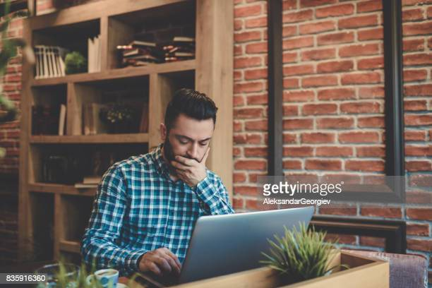 Serious and Worried Freelancer Working at his Favorite Coffee Place