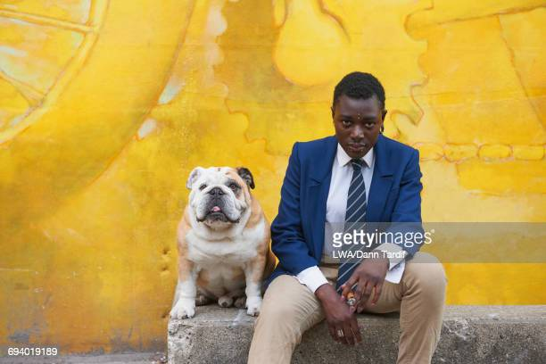 Serious androgynous Black woman sitting with dog near mural
