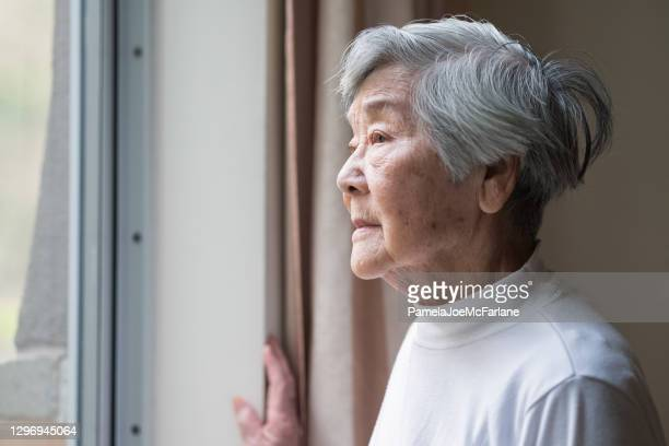 serious asian senior woman in 90s looking out of window - chinese ethnicity stock pictures, royalty-free photos & images