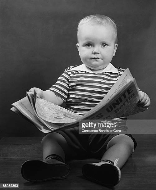 Serious baby holding newspaper