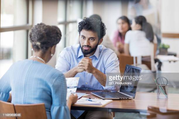 serious bank officer talking with customer - pamphlet stock pictures, royalty-free photos & images