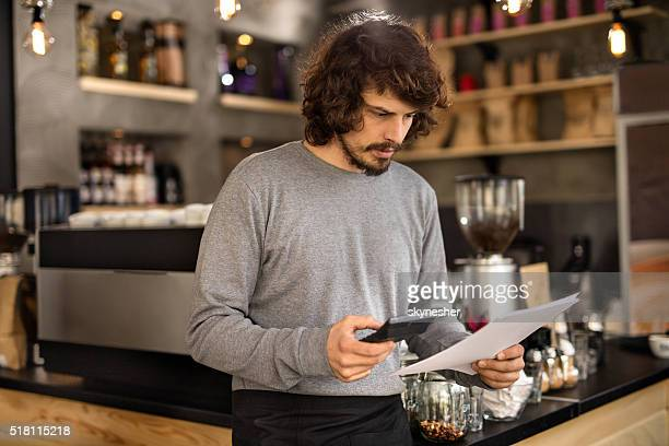 Serious barista calculating finances in a cafe.