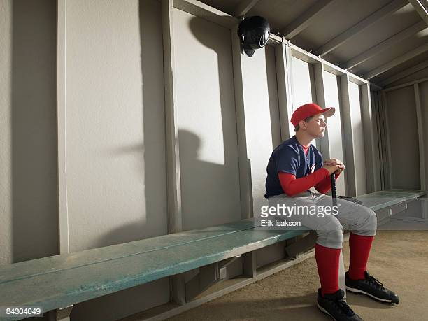 serious baseball player sitting in dugout - sports dugout stock pictures, royalty-free photos & images