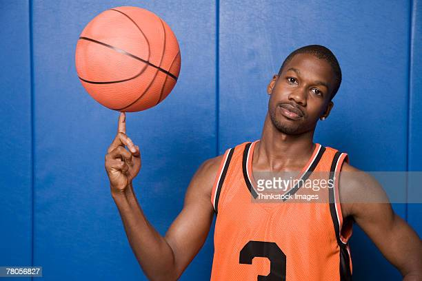 Serious basketball player spinning ball on finger