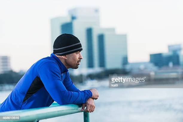 Serious black man in ski cap looking at city view