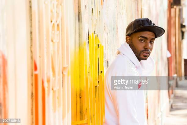 Serious Black man standing near gate