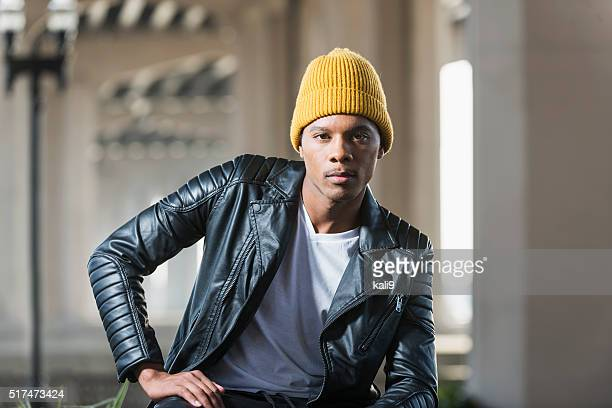 Serious black man wearing yellow beanie, leather jacket
