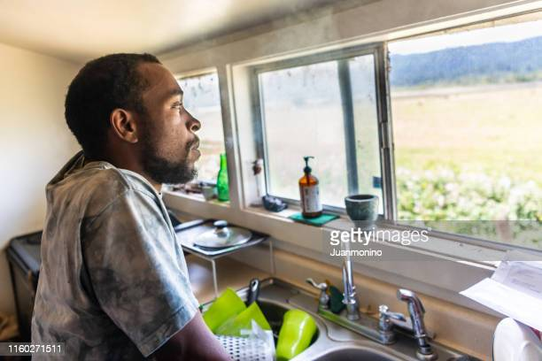 serious black mid adult man looking through a window - afro caribbean ethnicity stock pictures, royalty-free photos & images