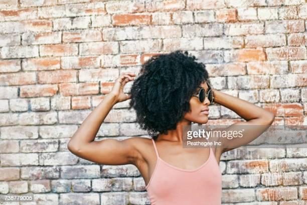 serious black woman near brick wall - mão no cabelo - fotografias e filmes do acervo