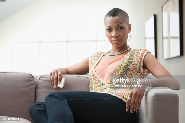 serious black woman sitting on sofa - attitude stock pictures, royalty-free photos & images