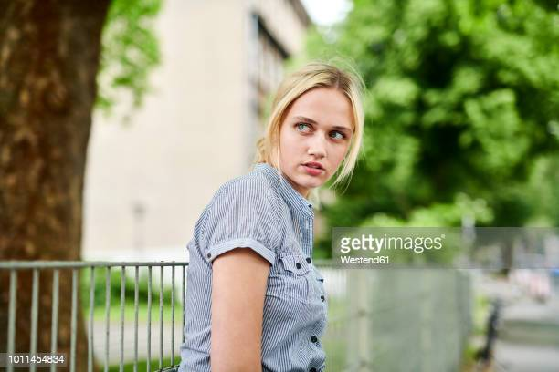serious blond young woman at a fence - displeased stock pictures, royalty-free photos & images