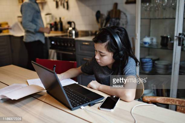 serious boy doing homework while using laptop and mobile phone at home - distance learning stock pictures, royalty-free photos & images