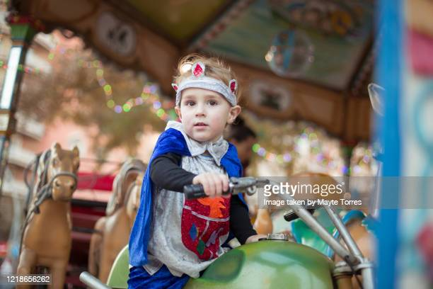 serious boy in a motorbike on a carousel dressed as a prince - reality kings stock pictures, royalty-free photos & images