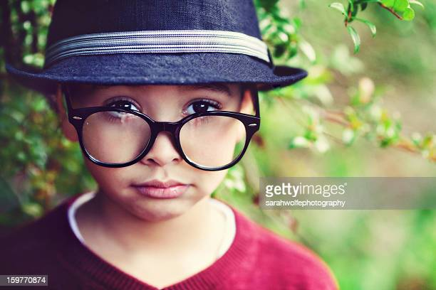 Serious boy in hat and glasses