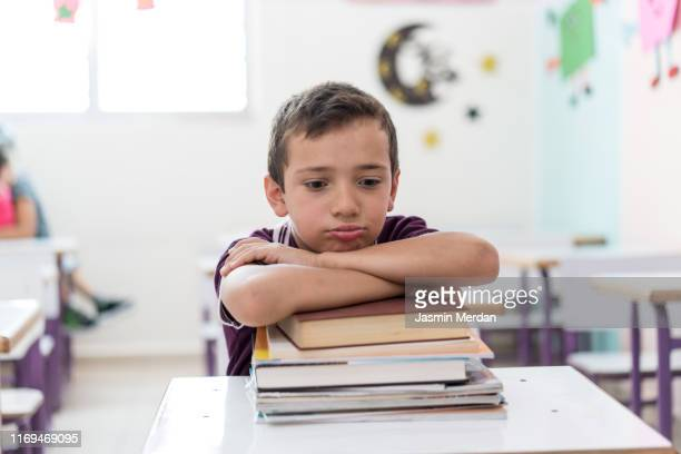serious boy in school - kind im grundschulalter stock-fotos und bilder