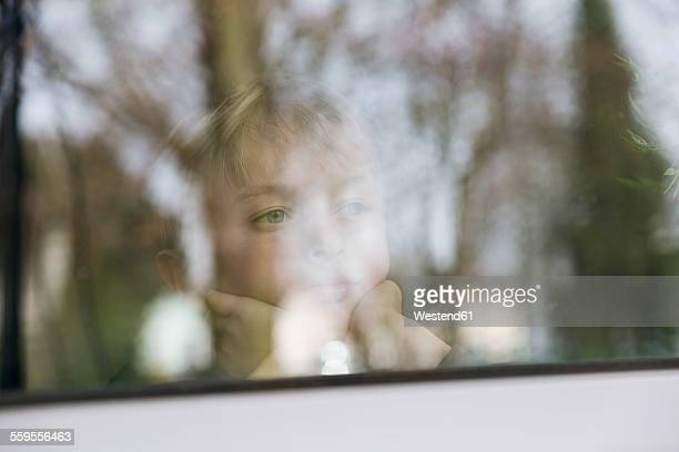Serious boy looking out of window