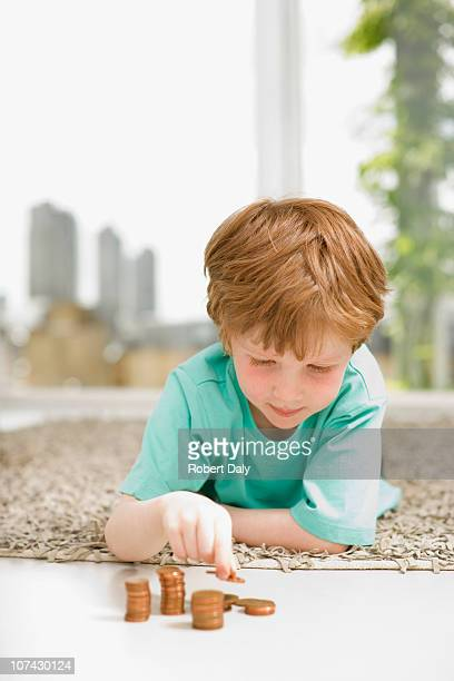 Serious boy stacking pennies on floor