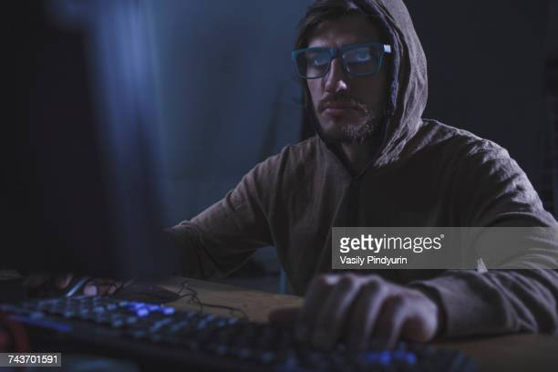 serious burglar wearing hooded shirt using computer at table - con man stock photos and pictures