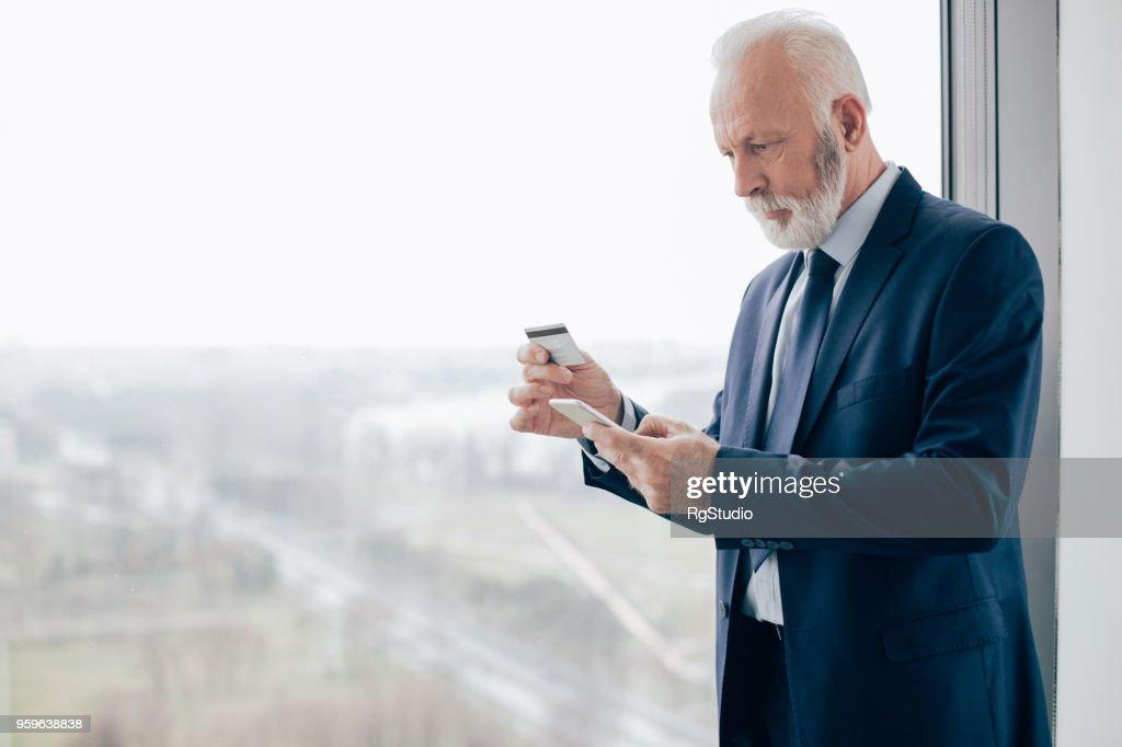 Ernsthaften Geschäftsmann mit Smartphone-Blick auf Kreditkarte : Stock-Foto
