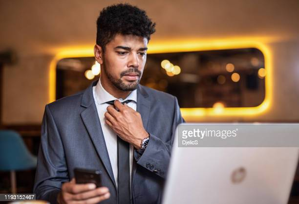 serious businessman adjusting a necktie before meeting. - adjusting necktie stock pictures, royalty-free photos & images