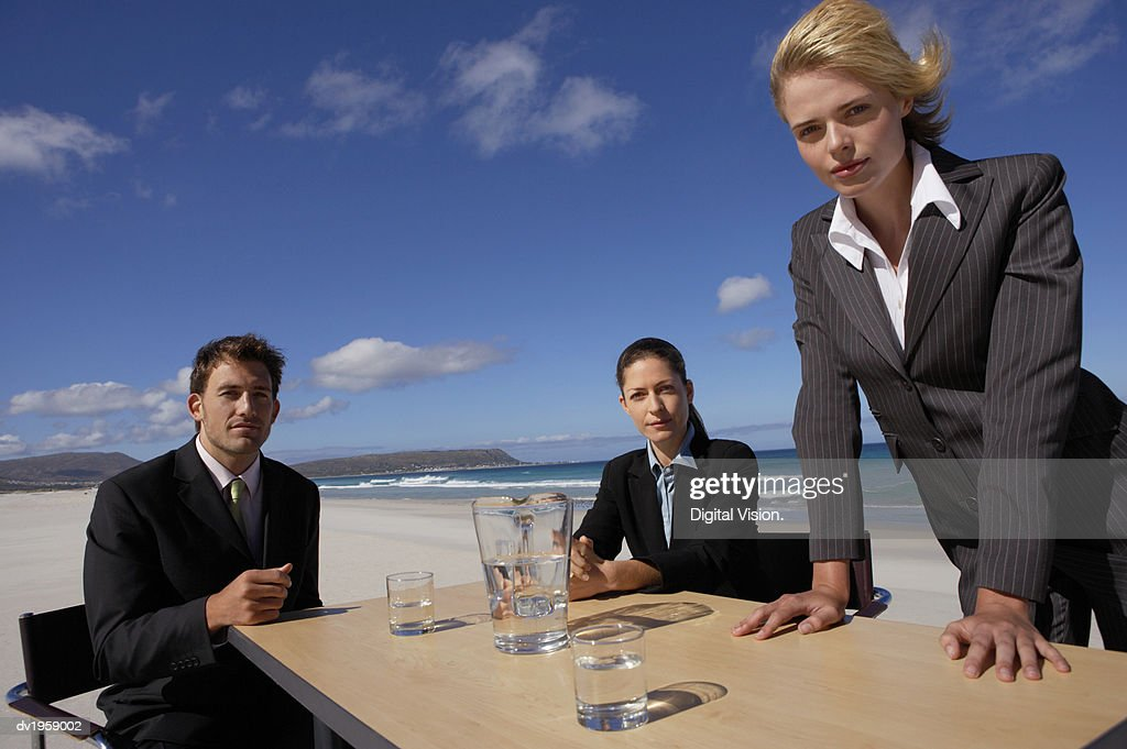 Serious Businessman and Businesswomen Having a Meeting Outdoors on a Beach : Stock Photo