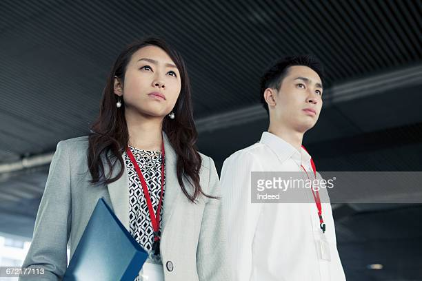 Serious businessman and woman looking away