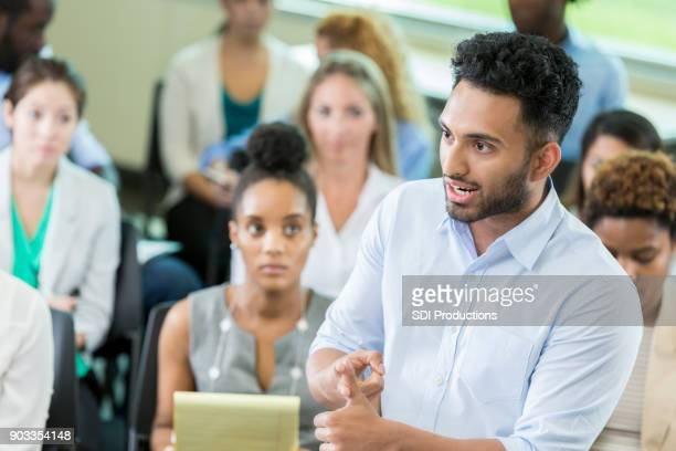serious businessman asks question during conference - conferenza stampa foto e immagini stock