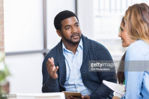serious businessman brainstorms with coworkers - book club meeting stock pictures, royalty-free photos & images