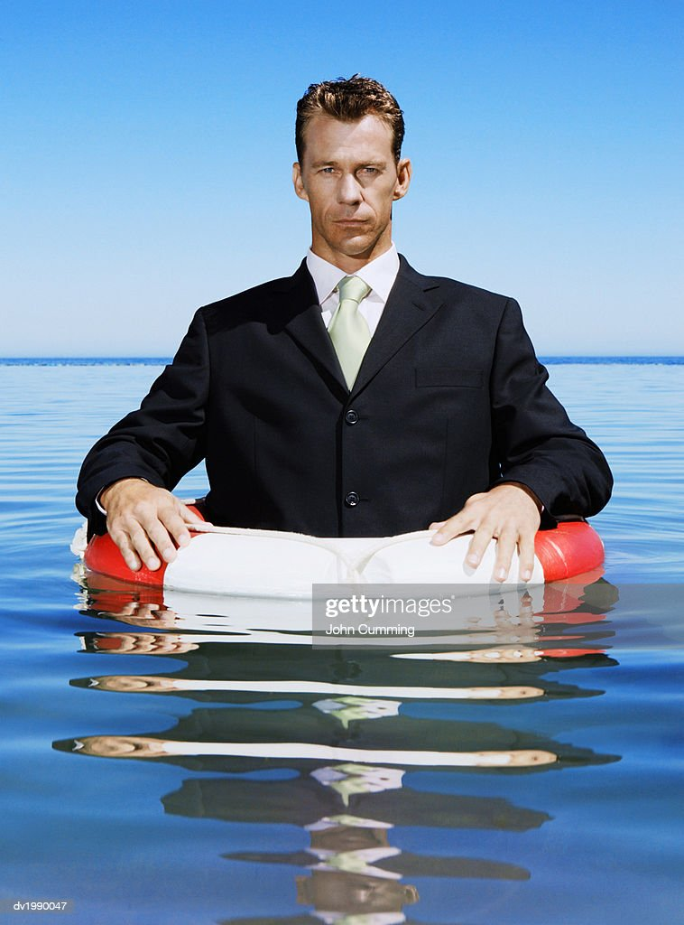 Serious Businessman Floating in the Sea with a Rubber Ring : Stock Photo